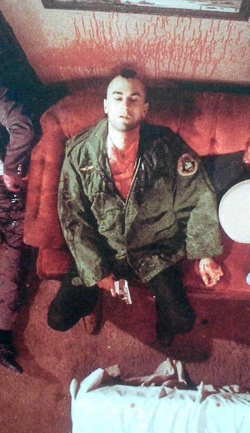 Travis Bickle, blutbedeckt mit einer Pistole in der Hand auf einem Sofa sitzend