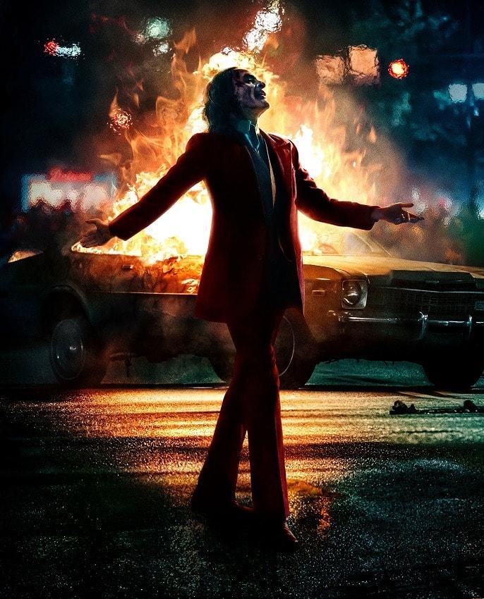 Arthur Fleck als Joker vor einem brennenden Auto