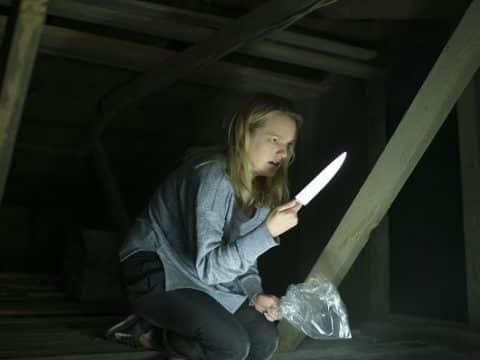 """Cecilia aus """"Der Unsichtbare"""" mit einem Messer bewaffnet auf dem Dachboden"""