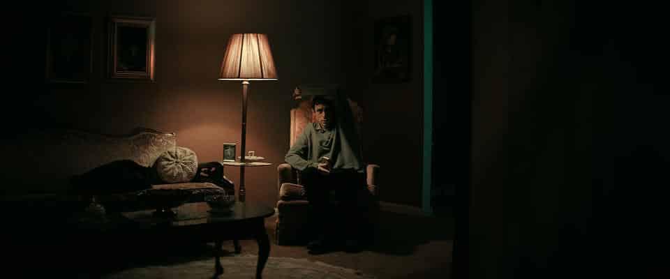 "Szene aus ""The Vigil"": Yakov sitzt im halbdunklen Raum im Sessel."